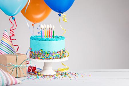 Gâteau d'anniversaire bleu, cadeaux, chapeaux et ballons colorés sur gris clair. Banque d'images - 80428271