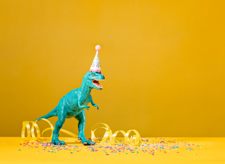Toy dinosaur with birthday party hat on a yellow background. Stock Photo