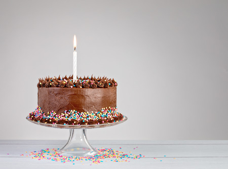 Chocolate birthday cake with colorful sprinkles and candle over white background. Stock Photo