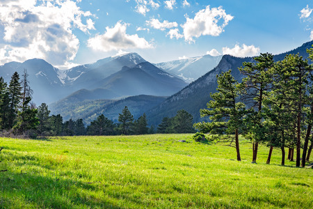 Idyllic summer landscape in Rocky Mountain National Park, colorado, with green mountain pastures and mountain range in the background. Stock Photo