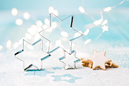 Sternplätzchenschneider und Zimtplätzchen auf den blauen Brettern besprüht mit Puderzucker und weich, unscharf, sternförmige Weihnachtslichter. Standard-Bild