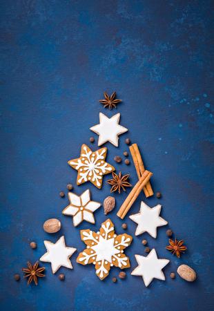 Lebkuchen-Schneeflocken und Zimtsternplätzchen mit Gewürzen in Form eines Weihnachtsbaums, über einem blauen Hintergrund.