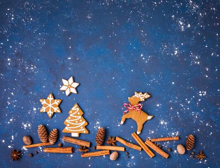 Lebkuchenplätzchen mit den Gewürzen, die eine schneebedeckte Weihnachtsszene mit Ren und Baum, über einem blauen Hintergrund schaffen.