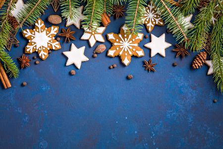 Weihnachtshintergrund mit Plätzchen, Tannenzweigen und Gewürzen auf dunkelblauem. Standard-Bild