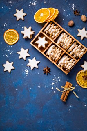 Traditionelle deutsche Stern-Plätzchen in einer Geschenkbox mit Gewürzen und getrockneten Orangen über einem blauen Hintergrund. Weihnachten oder Jom Kippur.