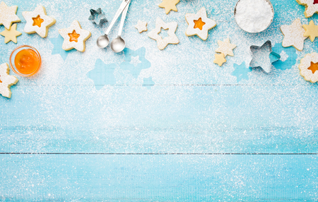 Christmas Linzer cookies border with icing sugar and apricot jam on a blue wooden background.