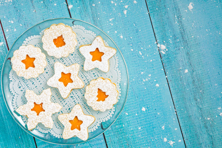 Weihnachten Linzer-Plätzchen mit Aprikosenmarmelade auf einem blauen hölzernen Hintergrund. Standard-Bild