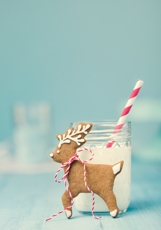 Cute gingerbread reindeer Christmas cookie with milk and straw over a blue background. Vintage syle. Standard-Bild