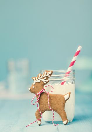 Nettes Lebkuchenren Weihnachtsplätzchen mit Milch und Stroh über einem blauen Hintergrund. Vintage-Stil.