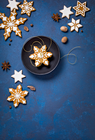Christmas background corner border with cookies and spices on an abstract painted blue backdrop. Standard-Bild