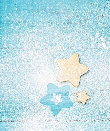 Sternförmige Weihnachts-Linzer-Plätzchen mit Puderzucker auf einem blauen Hintergrund.