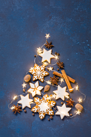 Christmas cookies in the shape of a tree with lights on an abstract painted blue background Standard-Bild