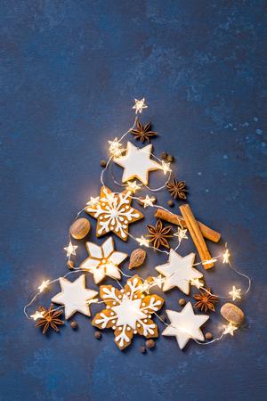 Weihnachtsplätzchen in der Form eines Baums mit Lichtern auf einem abstrakten gemalten blauen Hintergrund Standard-Bild