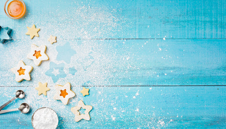 Decorating Christmas Linzer cookies with icing sugar and apricot jam on a blue wooden background. Standard-Bild