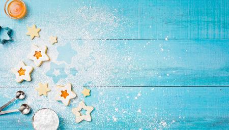 Verzierung von Weihnachten Linzer-Plätzchen mit Puderzucker und Aprikosenmarmelade auf einem blauen hölzernen Hintergrund.