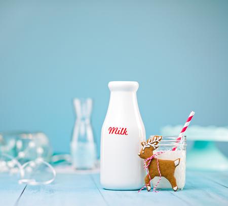 Nettes Lebkuchenren Weihnachtsplätzchen mit Milch und Stroh über einem blauen Hintergrund. Standard-Bild