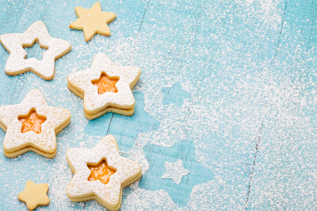 Christmas Linzer cookies with apricot jam and icing sugar on a blue background.