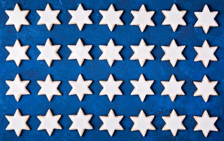 Zimt-Stern-Plätzchen-Weihnachtsmuster auf einem blauen Hintergrund. Standard-Bild