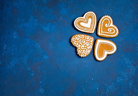 Vier Lebkuchen-Herz-Weihnachtsplätzchen auf einem blauen Hintergrund.