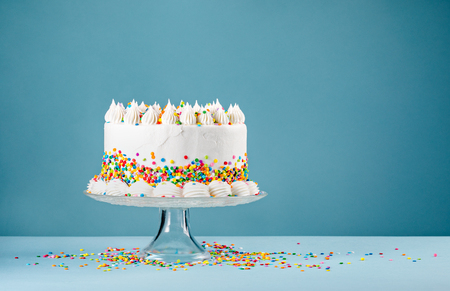 White Birthday cake with colorful Sprinkles over a blue background. Stok Fotoğraf