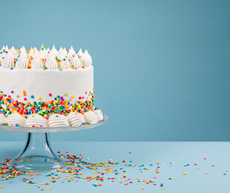 White Birthday cake with colorful Sprinkles over a blue background. Banque d'images