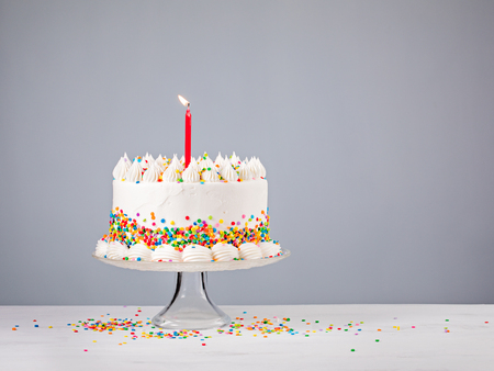 White Birthday cake with colorful Sprinkles and red candle over a gray background. Stock Photo