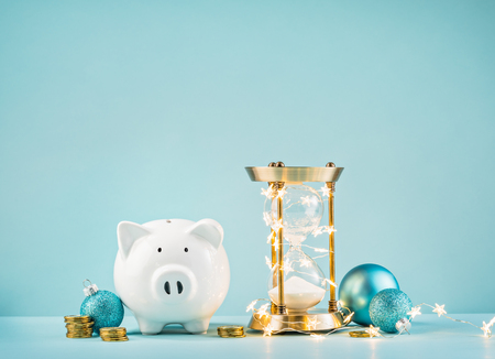 Piggy bank and rustic hourglass wrapped in lights on a blue background. Countdown to save for the Christmas gift giving season concept. Фото со стока