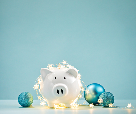 White Piggy bank wrapped in a string of Christmas lights over a blue background. Saving concept. Archivio Fotografico