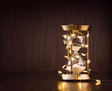 Christmas or new years countdown. Rustic Hourglass wrapped in lights with sand trickling through on a wooden background.