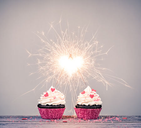 Two valentines day buttercream Cupcakes with sparklers creating a heart shape celebrating love concept Standard-Bild - 115560424