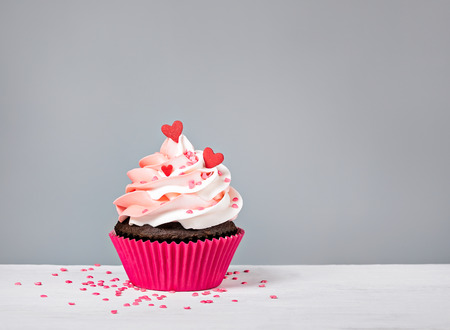 Valentines Day Cupcake treat with buttercream icing and heart sprinkles on a grey background Standard-Bild - 115560425