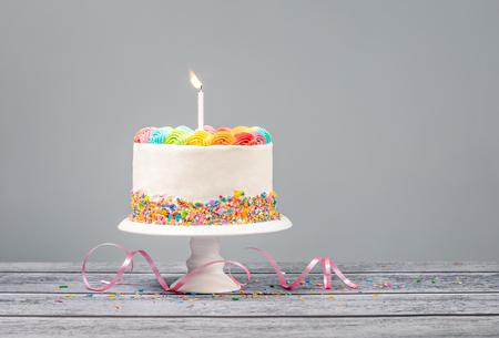 Pastel de cumpleaños blanco con glaseado de arcoíris, chispitas de colores y una vela sobre un gris Foto de archivo