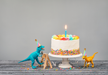 Hungry toy dinosaurs wearing hats and holding forks next to a birthday Cake on a gray