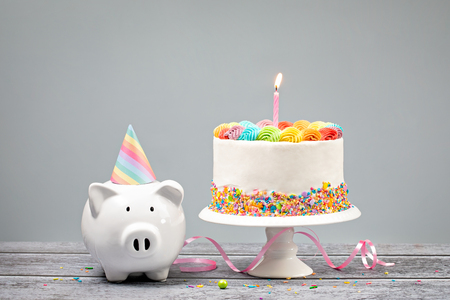 Birthday Money Concept with Rainbow Cake, one Candle and cute Piggy Bank over a neutral