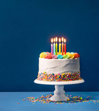 Birthday Cake With Rainbow Icing Colorful Sprinkles And Lit Candles Over A Blue Stock Photo