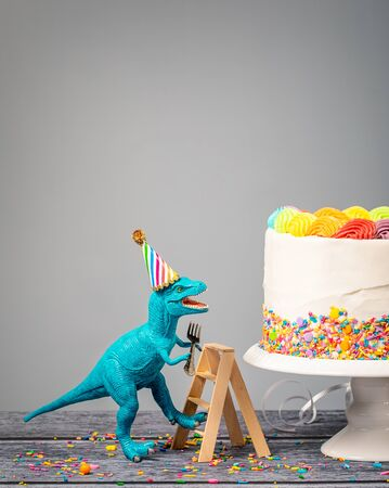 Silly toy dinosaur wearing a hat and holding a fork climbing a ladder to a birthday Cake on a gray