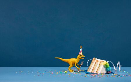 Toy Dinosaur holding a fork next to a slice of birthday cake on a blue