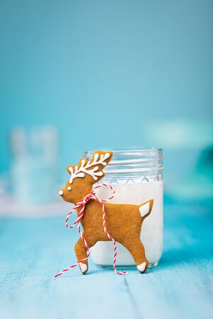 Cute gingerbread reindeer Christmas cookie with milk over a blue background. Vintage syle.