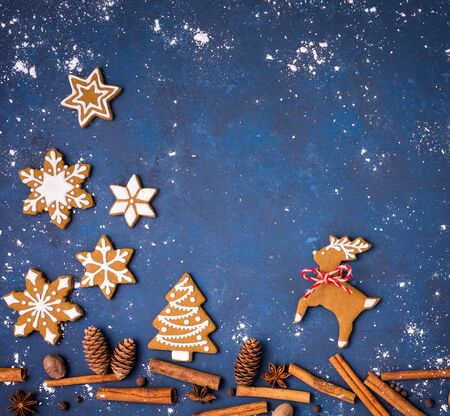 Gingerbread cookies with spices creating a snowy Christmas forest scene with reindeer and tree, over a blue background. 스톡 콘텐츠