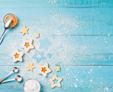 Decorating Christmas Linzer cookies with icing sugar and orange apricot jam on a blue background. Stock Photo