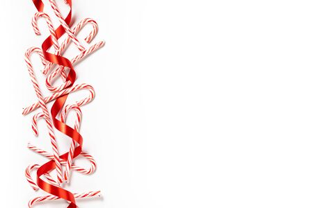 Christmas candy cane border with red ribbon over a white