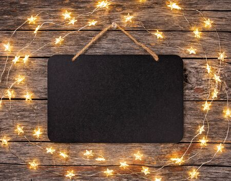 Blank chalkboard sign with string lights hanging from wooden background.