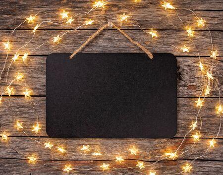 Leeres Tafelschild mit Lichterketten, die vom Holzhintergrund hängen