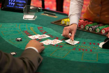 Krupier kładzie kartę na stole do blackjacka