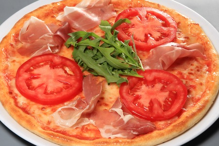Pizza with prosciutto, tomatoes and arugula , closeup Reklamní fotografie