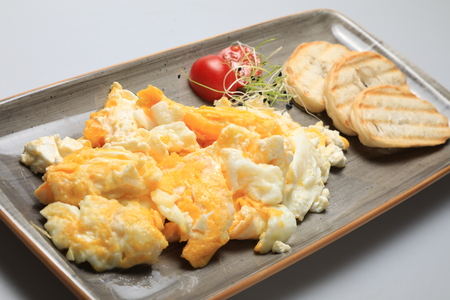 Scrambled eggs wioth some bread and cherry tomatoes 免版税图像