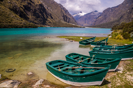 ancash: Huaraz, PERU: Six green boats are waiting to be sailed across the blue glacier lagoon in the Peruvian Andes. Huaraz is a popular tourist destination for alpine hiking. Stock Photo
