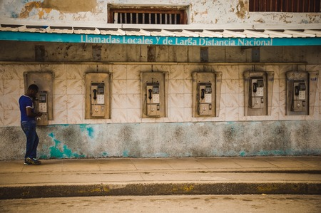 telephones: CUBA in December 2015: A male person uses a public payphone to make a call. Public phones are the only telephones for many people in Cuba, international calls are expensive.