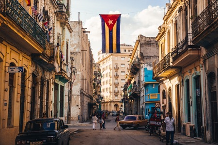 communists: Havana, Cuba in December 2015: A cuban flag with holes waves over a street in Central Havana. La Habana, as the locals call it, is the capital city of Cuba Editorial