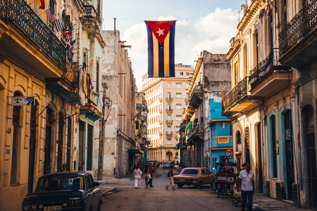 habana: Havana, Cuba in December 2015: A cuban flag with holes waves over a street in Central Havana. La Habana, as the locals call it, is the capital city of Cuba Editorial